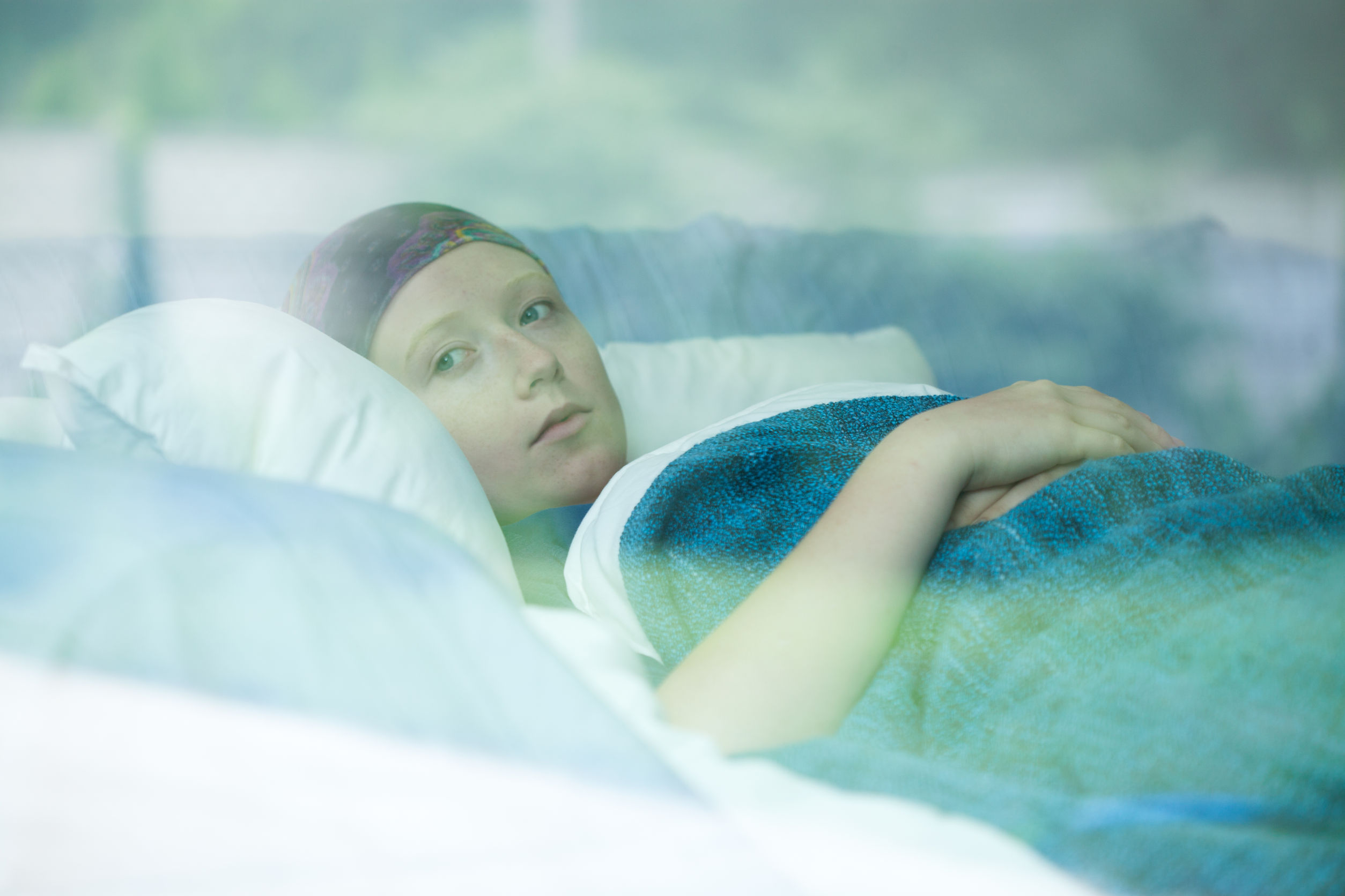 Young female cancer patient lying on the bed looking out the window