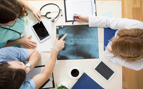 Doctors sitting around the table and interpreting x-ray image